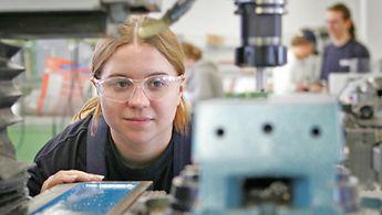 Eine junge Frau arbeitet an einer Maschine