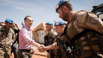 Außenminister Maas schüttelt die Hand eines in Mali stationierten Bundeswehrsoldaten.
