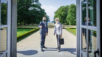 Zwei Menschen stehen einander zugewandt auf einer Treppe, dahinter ein Garten und Bäume.