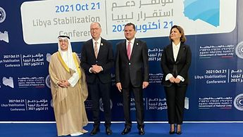 Three men and a woman. The backgroung banner says 2021 Ort 21 Libya Stabilization Conference steht